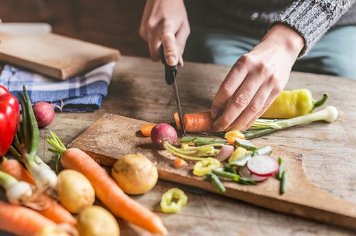 Close up of a pair of hands cutting up veggies, including carrots potatoes, and others