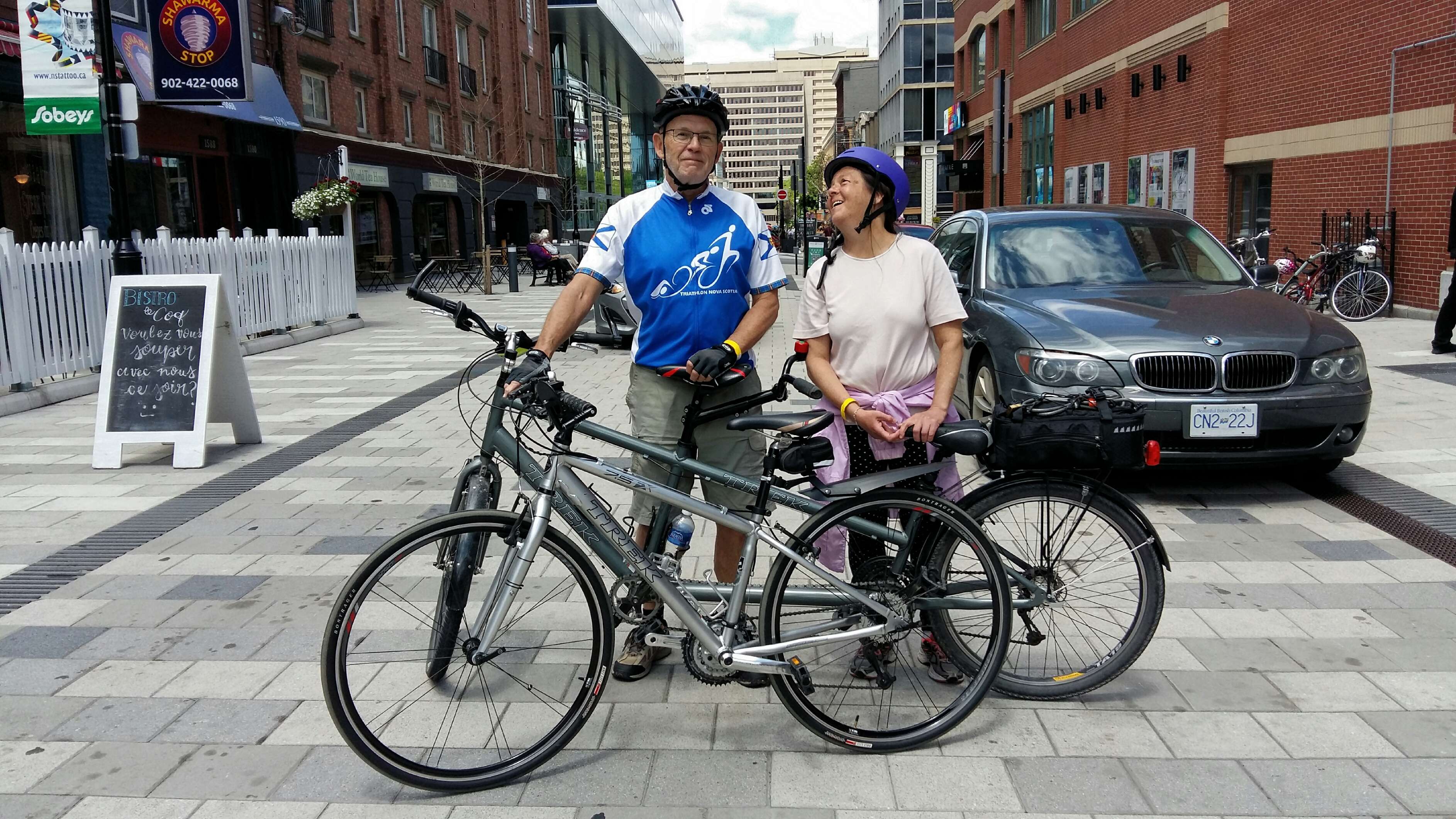 A man and woman stand with a tandem bike and standard bike in front of them on a downtown street