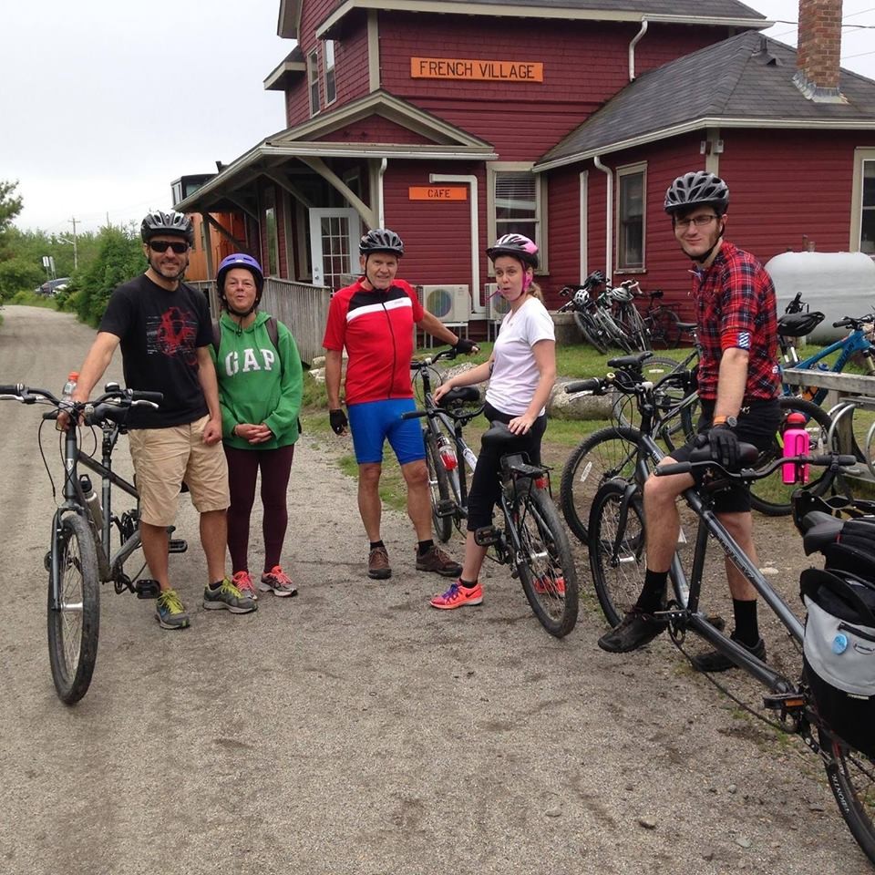 A group of 5 people stand with tandem bikes on a trail in front of a cafe