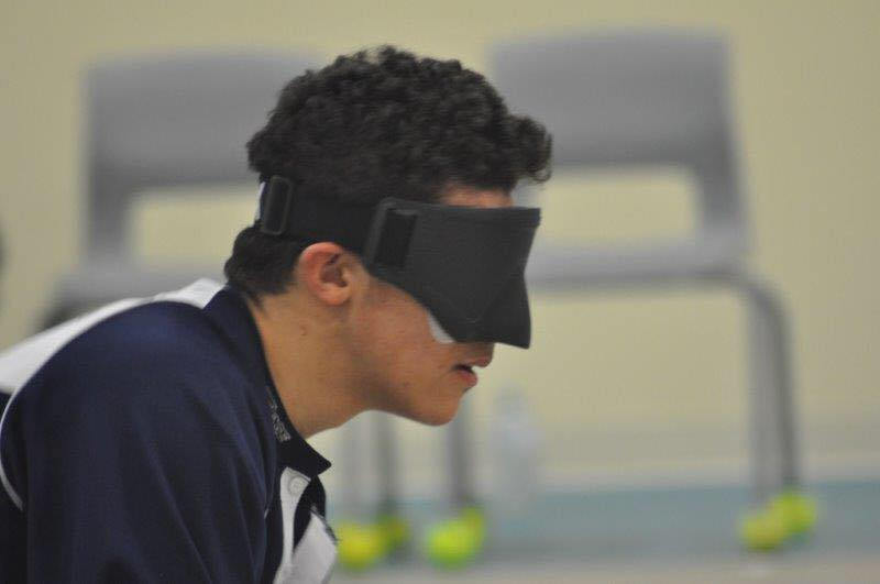 profile of Mason Smith, of the NS team wearing eyeshades, appearing focused on the goalball court.  Courtesy of Stephen Burke.