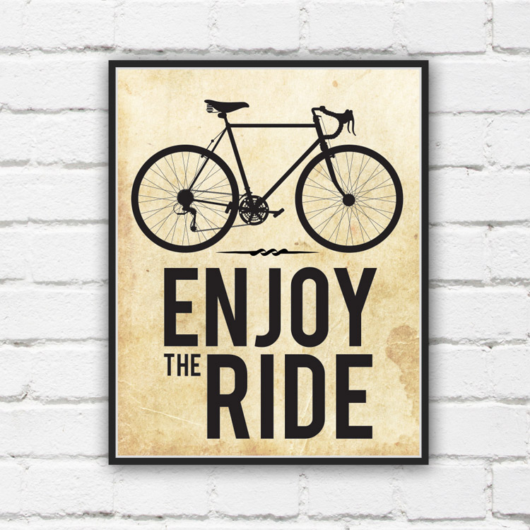 Enjoy the Ride in bold black text below an outline of a bicycle against a white brick wall
