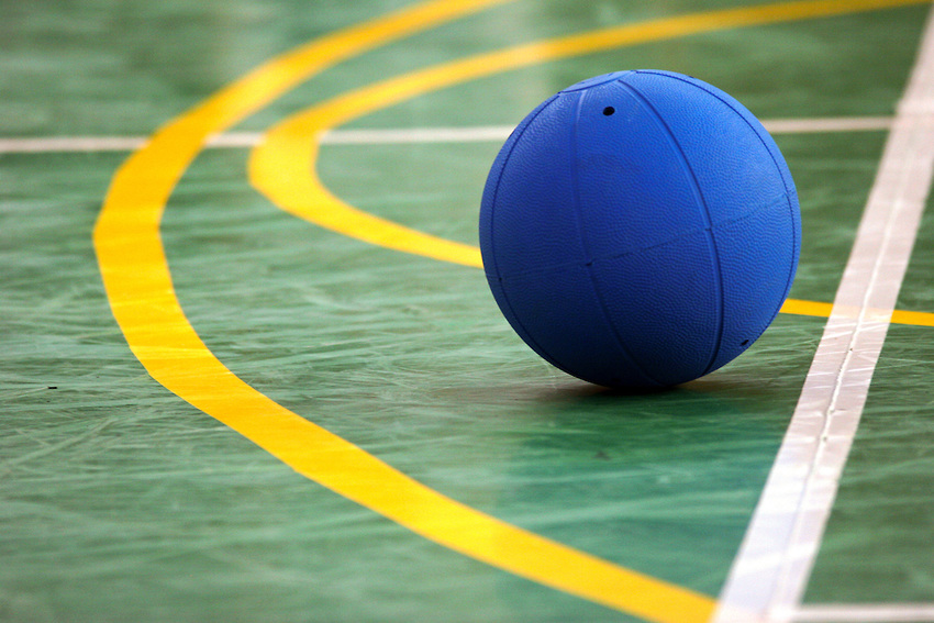blue goalball on a green gym court floor