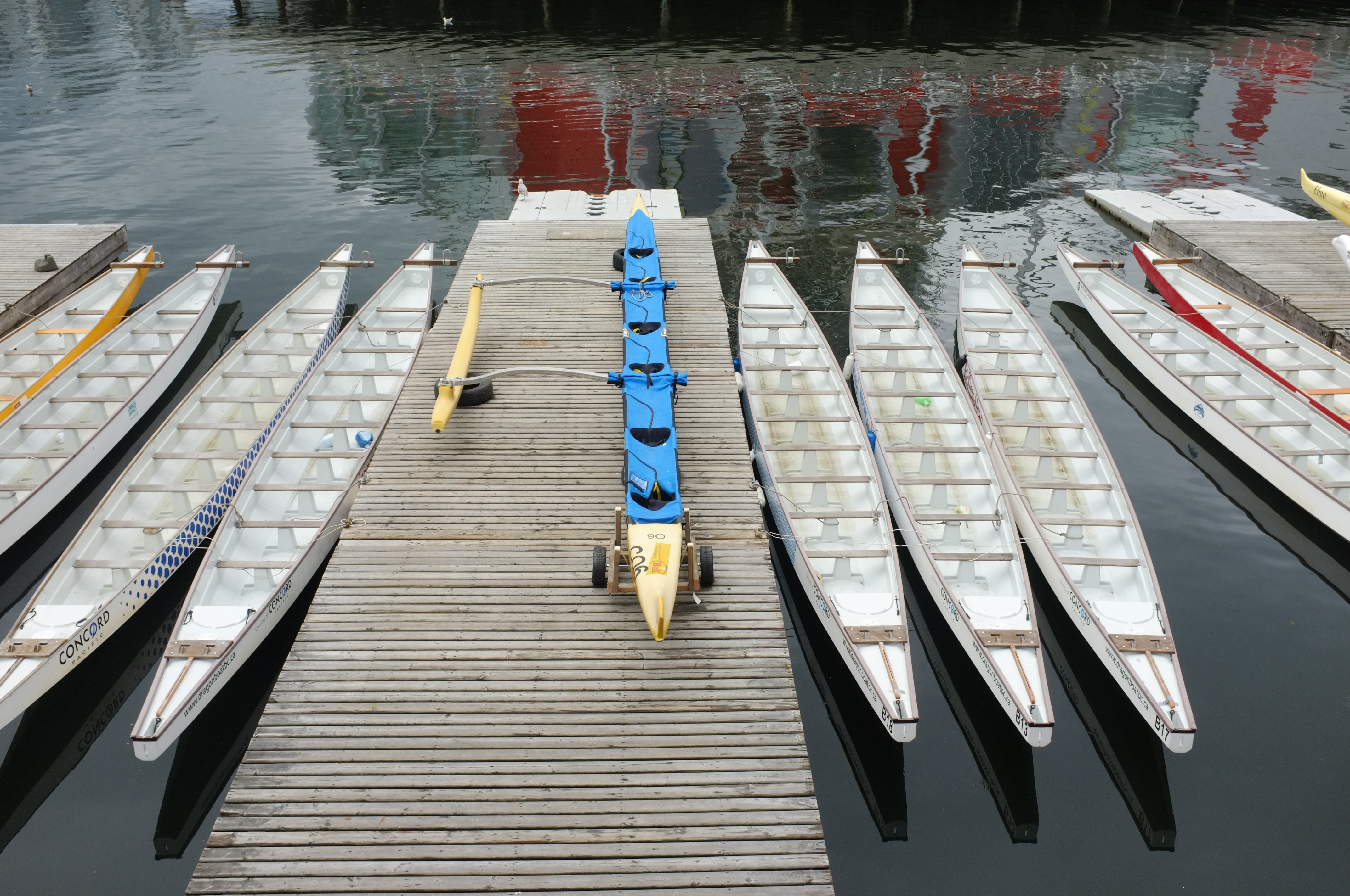 9 long dragon boats sitting empty in the water next to a dock