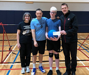 4 people in gymnasium holding goalball and cheque