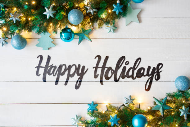 Happy holidays in grey-black handwriting style text in front of whitewashed wood and bordered by evergreen leaves, blue-themed holiday ornaments (like stars, trees, and snowflakes) and white lights