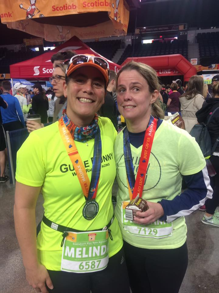 A runner and guide in neon green shirts show off their finisher medals and sport big smiles